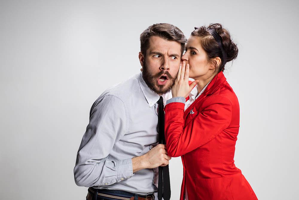 Kvinne hvisker hemmelighet til mann